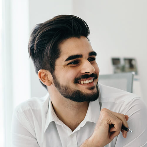 Ein lächelnder Mann mit schwarzem Haar und Bart
